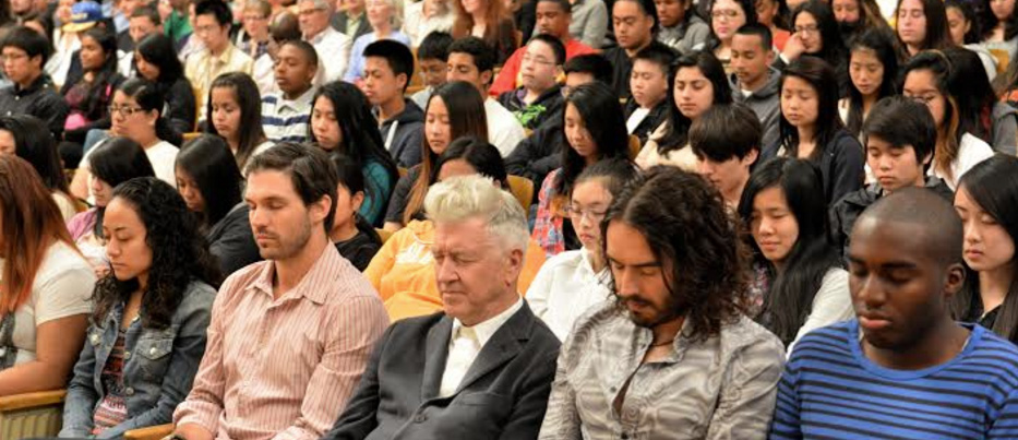 David Lynch and Russell Brand practicing Transcendental Meditation with a large group of students in San Francisco.